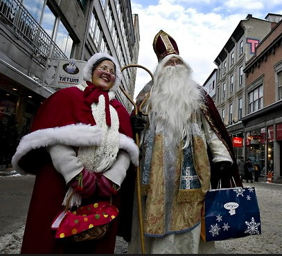 Père and Mère Noël stroll the streets of Quebec City. Credit- Christinne Muschi for The New York Times