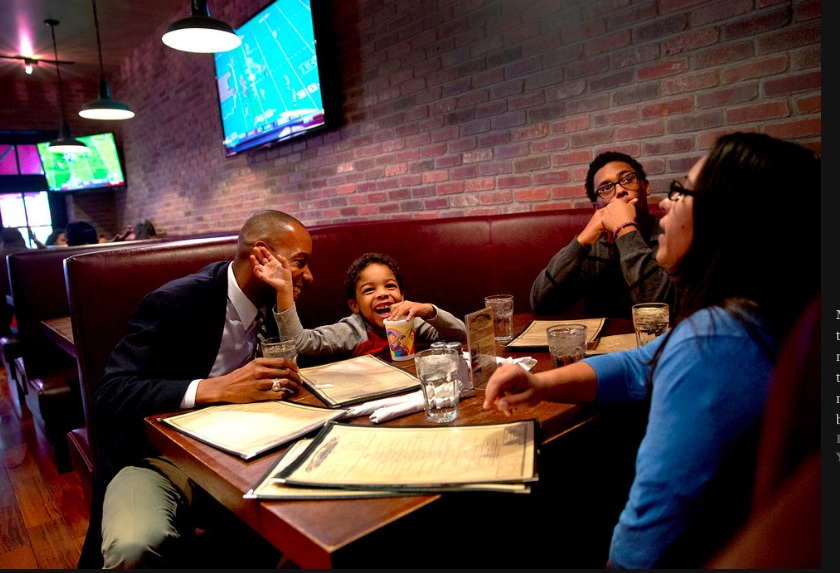 Mr. Hill, left, with Ms. Perez and the children at a Harlem restaurant. Photo: Beatrice de Gea for The New York Times