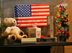 "A teddy bear, a flag proclaiming ""We will survive,"" and a model of the twin towers are among the objects collected from a post-Sept. 11 vigil that are now on display at the 9:11 Memorial Museum. Photo- The New York Times."