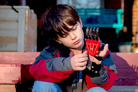 Ethan Brown, 8, of Opelika, Ala., was born with two fingers missing on his left hand. Now he wears a Cyborg Beast in black and red, his school colors. Credit Kevin Liles NYT
