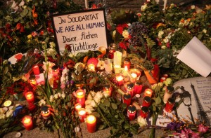 Hand written notes lie among flowers and candles at the French Embassy-